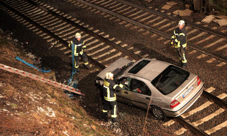 Car falls from bridge onto train tracks in deadly accident