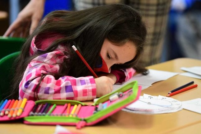 A child wearing a mask scribbles in a book in a school class.
