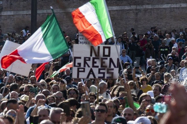 People wave national flags during a protest in central Rome