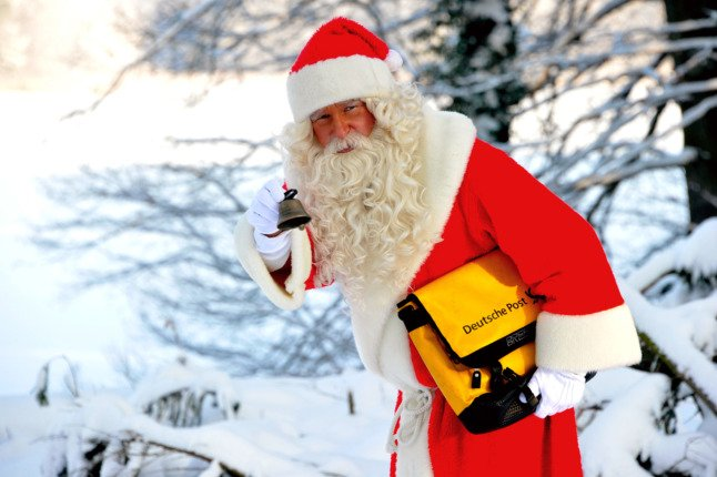 A man dressed as Santa delivers post
