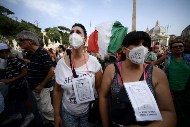 Protesters hold an Italian flag as they take part in a demonstration against the green pass in Piazza del Popolo in Rome on July 24, 2021.